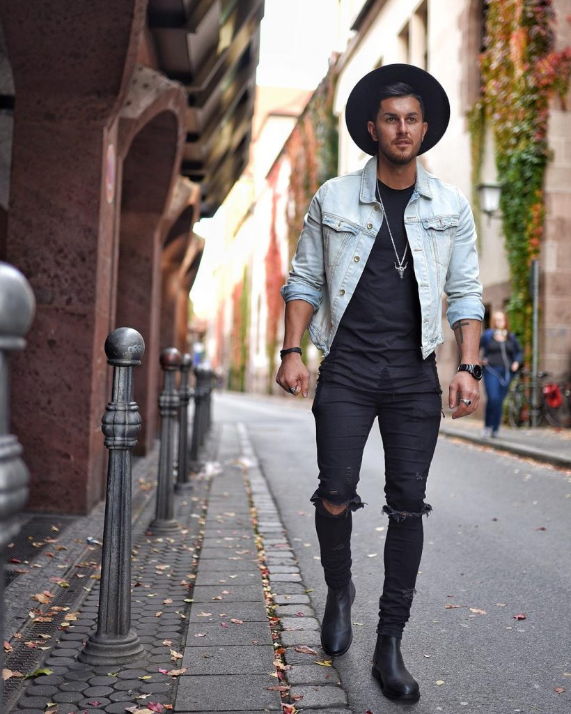 Denim jacket, black tee, dark jeans, fedora hat, and Chelsea boots