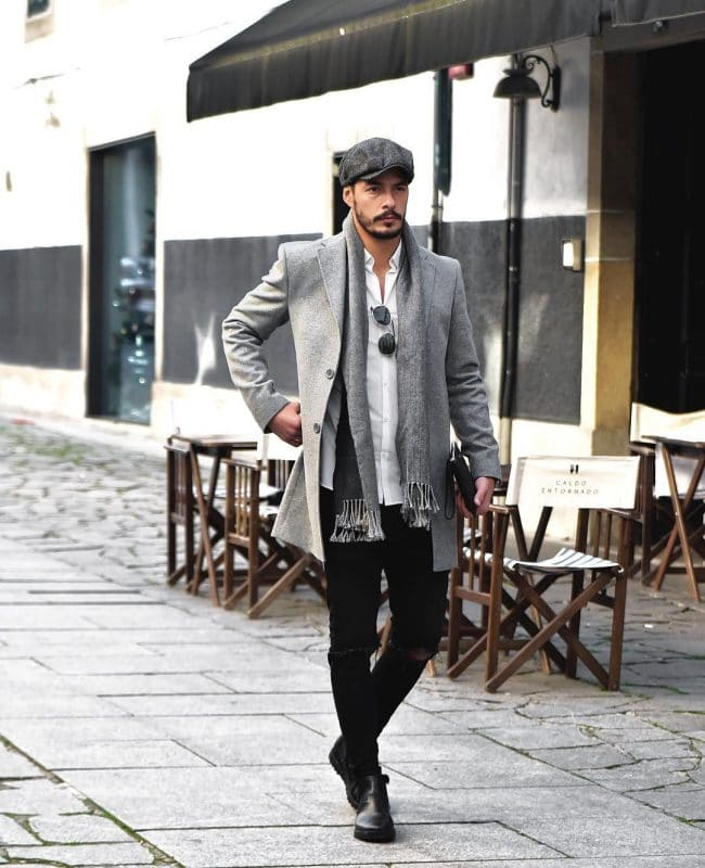 Gray beret cap, wool overcoat, white shirt, scarf, black jeans and leather boots