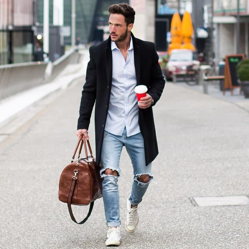 Black overcoat, light blue shirt, blue jeans and white canvas shoes
