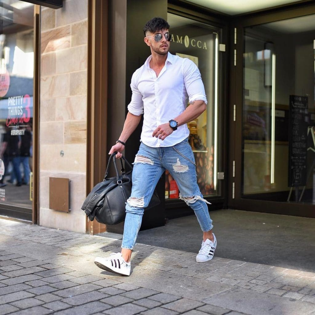 button-down white shirt, blue ripped jeans, and white sneaker
