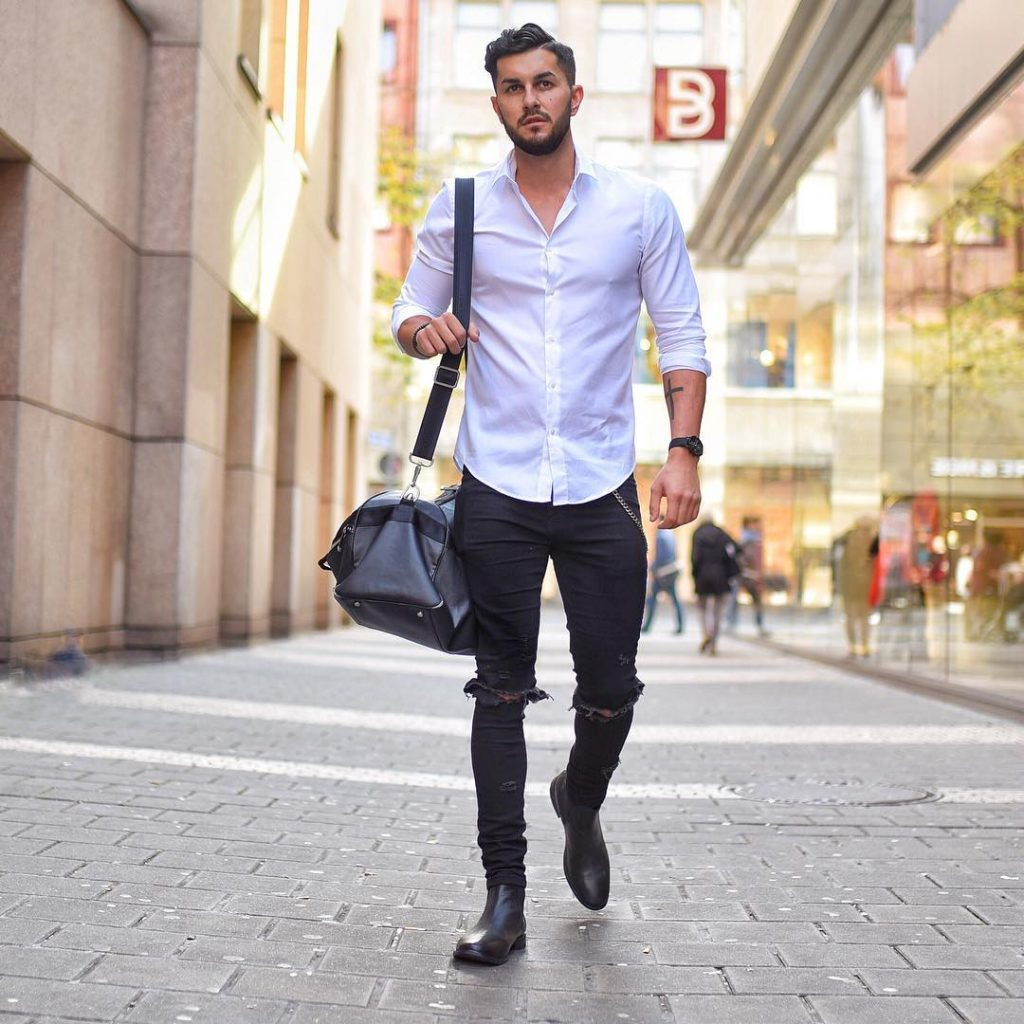 White button-down shirt, black ripped jeans, leather gym bag, and Chelsea boots