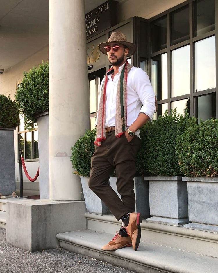 White button-down shirt, scarf, brown trousers, panama hat, and dress shoes