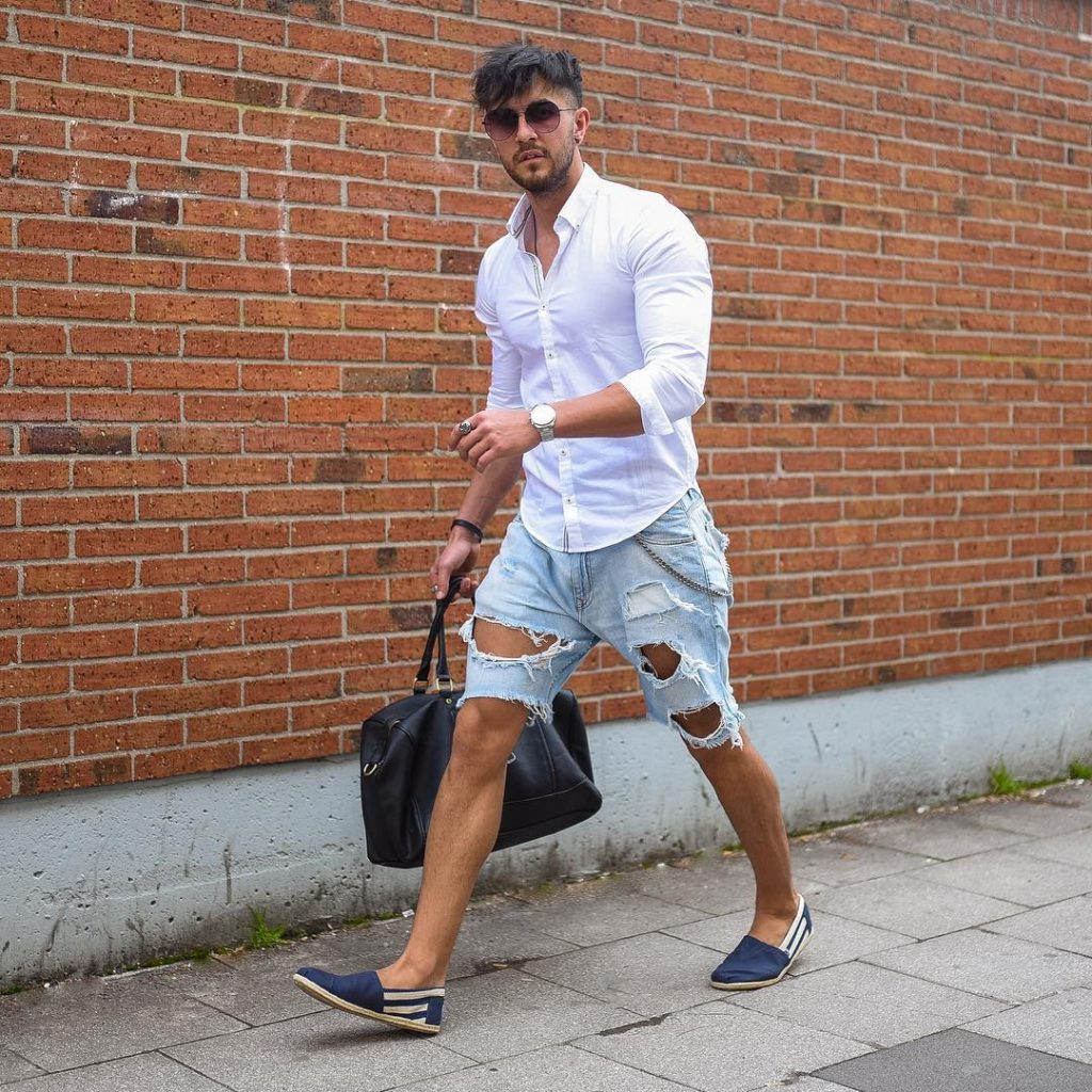 White button-down shirt, blue ripped short jeans, and espadrilles