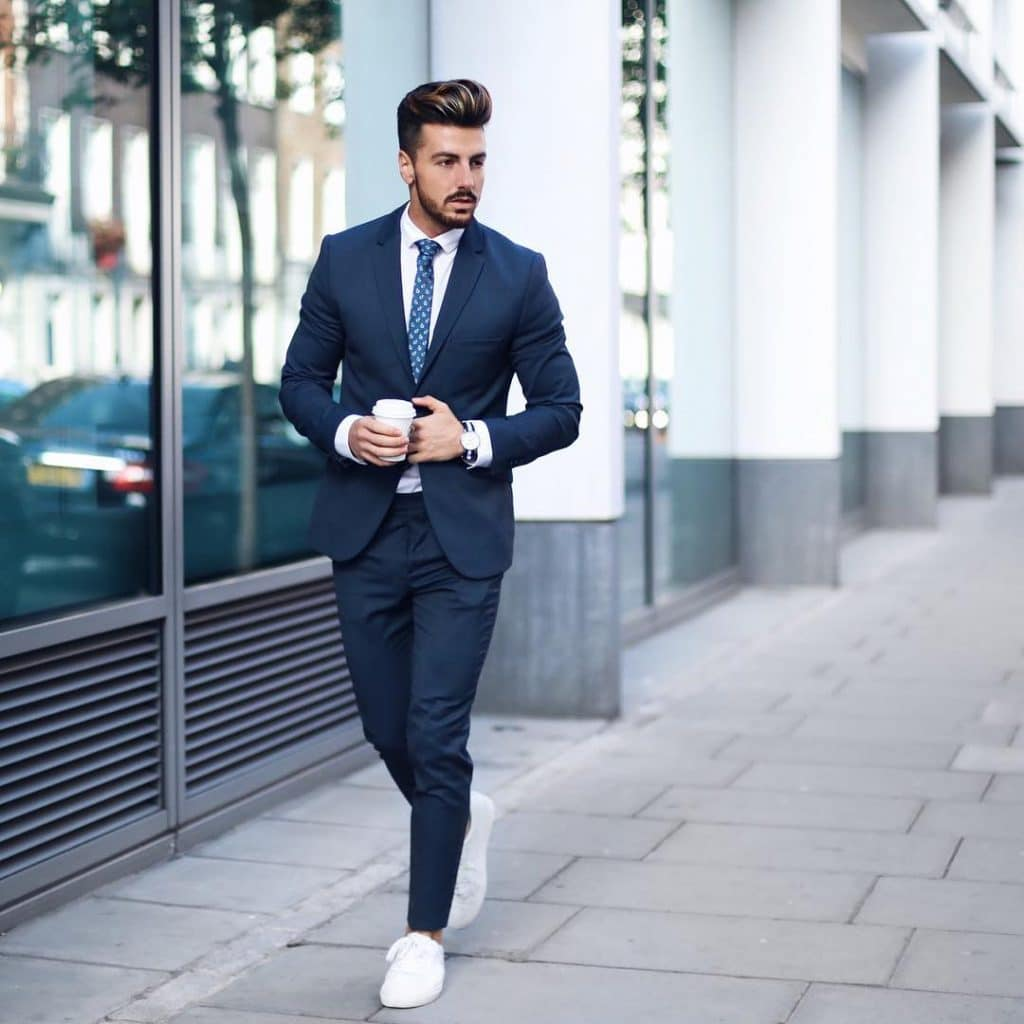 Dark blue suit, white shirt, dotted tie, and white sneaker