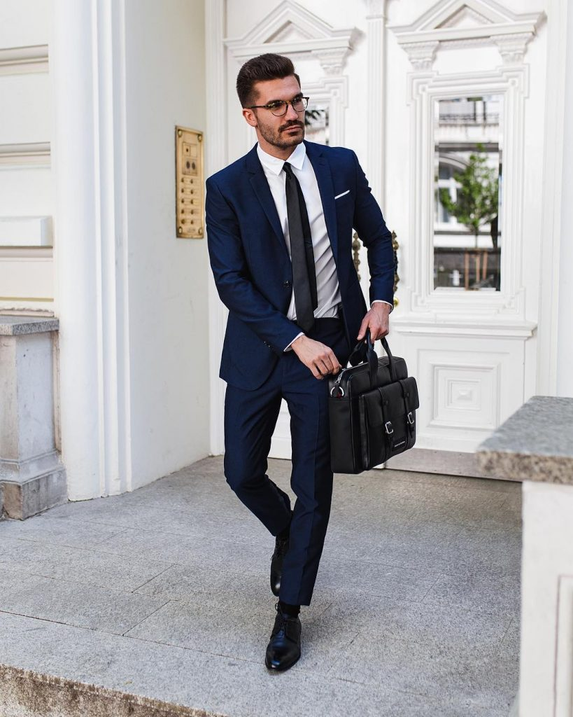 Dark blue suit, white shirt, black tie, black socks, and leather dress shoes