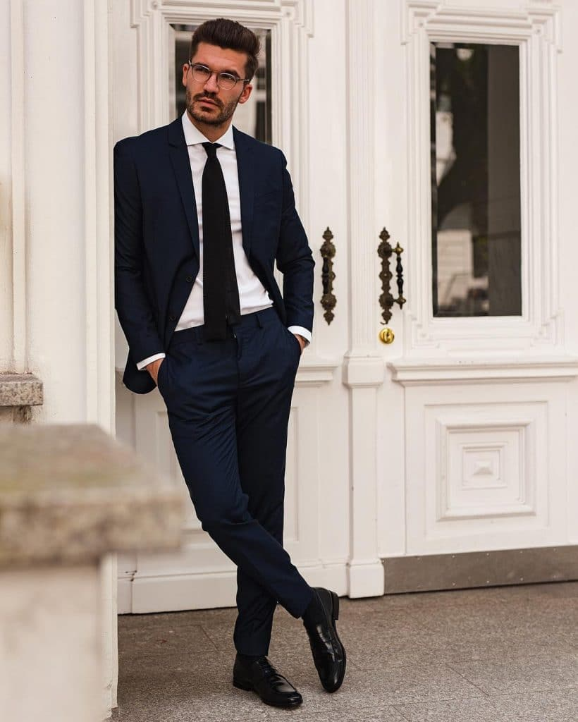 Dark blue suit, white shirt, black tie, and leather dress shoes
