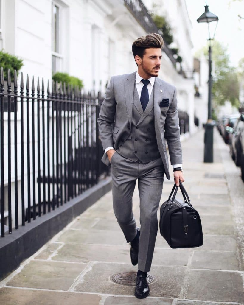 Gray wool single breasted suit with vest, white shirt, blue tie, black socks, and Oxford leather shoes