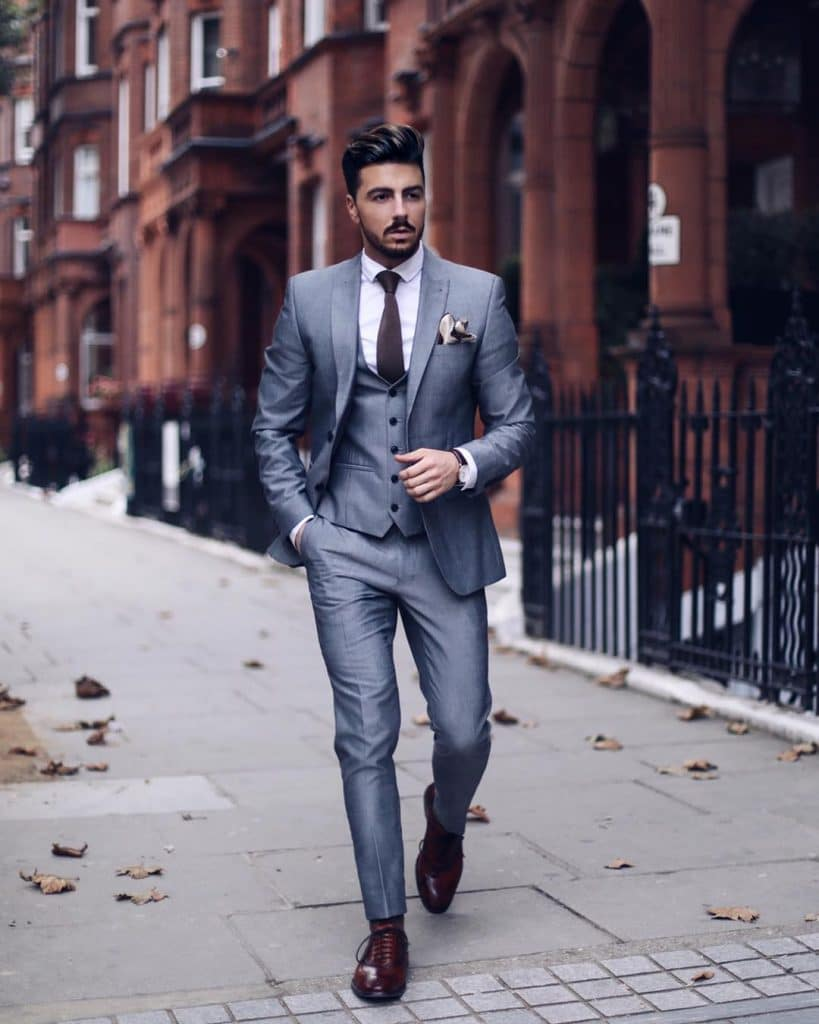 Gray wool single breasted suit with vest, white shirt, brown tie, and brown Oxford dress shoes