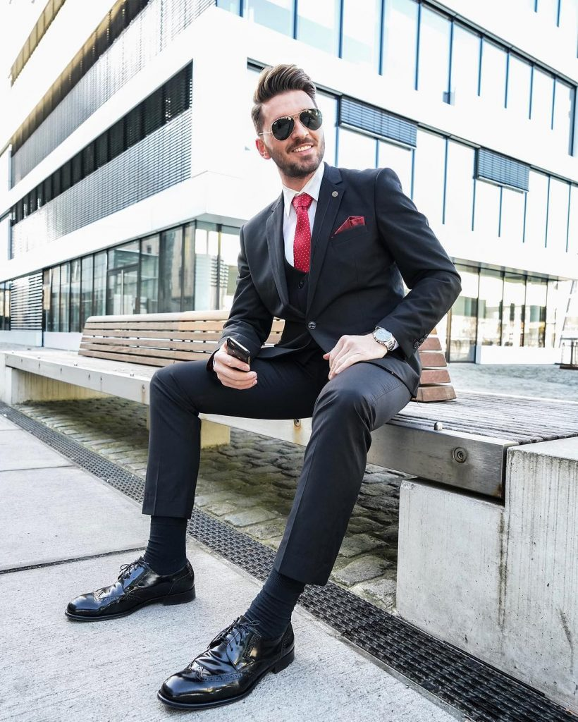 Black single breasted suit with vest, black shirt, red dotted tie, black socks, and black brogue derby shoes
