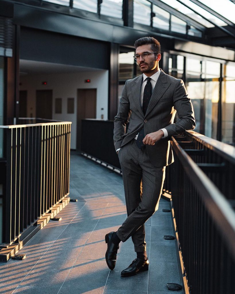Gray pinstripe suit, white shirt, black tie, and double monk strap shoes
