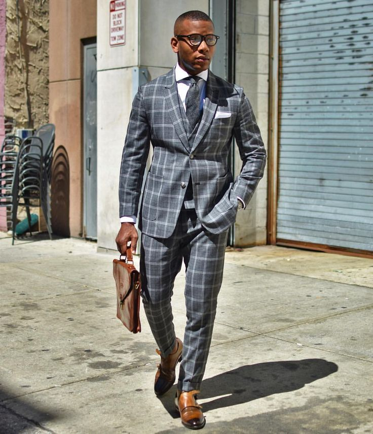 Gray checked suit with a vest, white shirt, gray tie, and brown double monk strap shoes