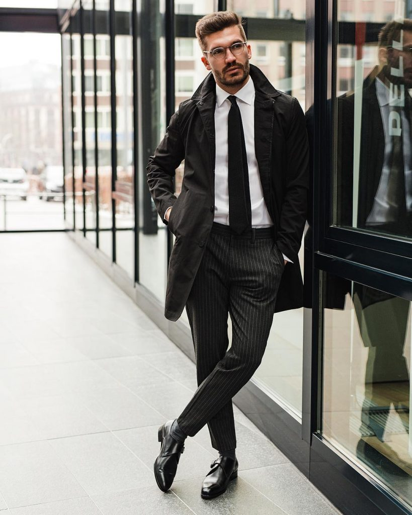 Black trench coat, white shirt, black tie, pinstripe dress pants, and double monk strap shoes