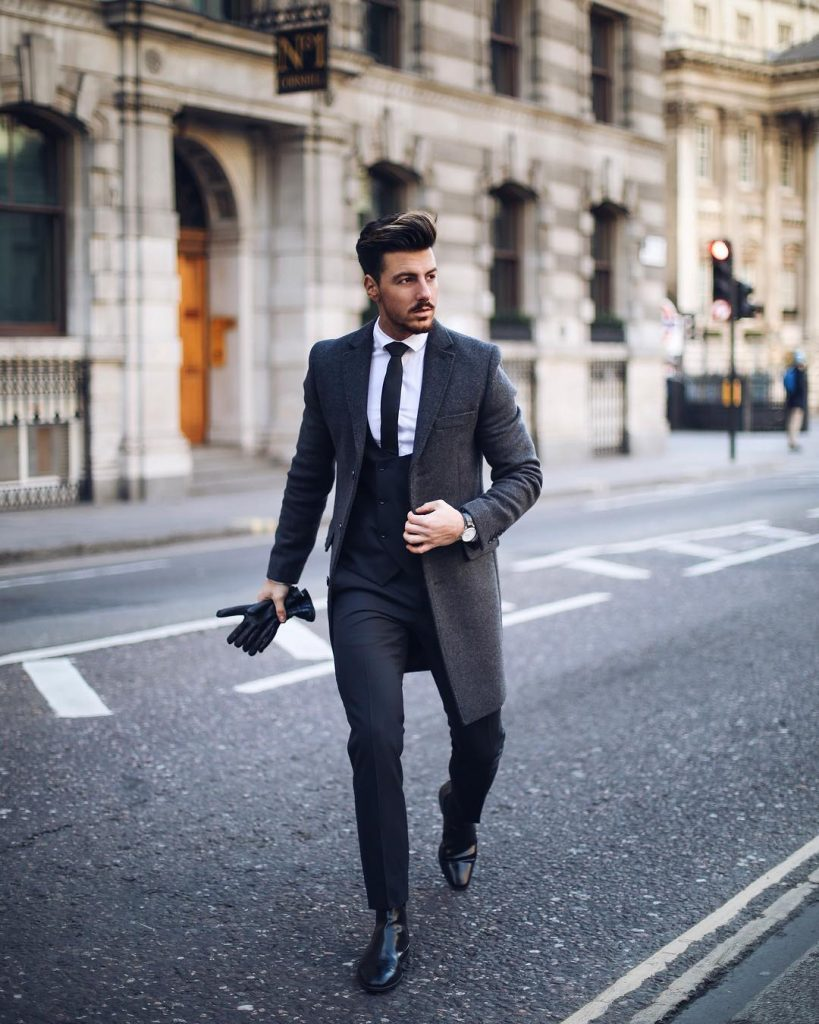 Gray wool overcoat, vest, white shirt, black tie, and leather boots