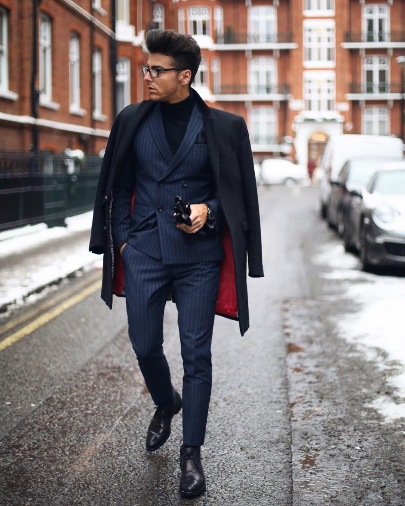 Dark blue overcoat, blue pinstripe suit, sweater, and leather chukka boots