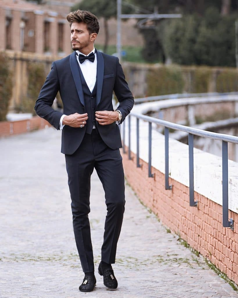 Dark blue formal suit with a vest, bow tie, and loafers