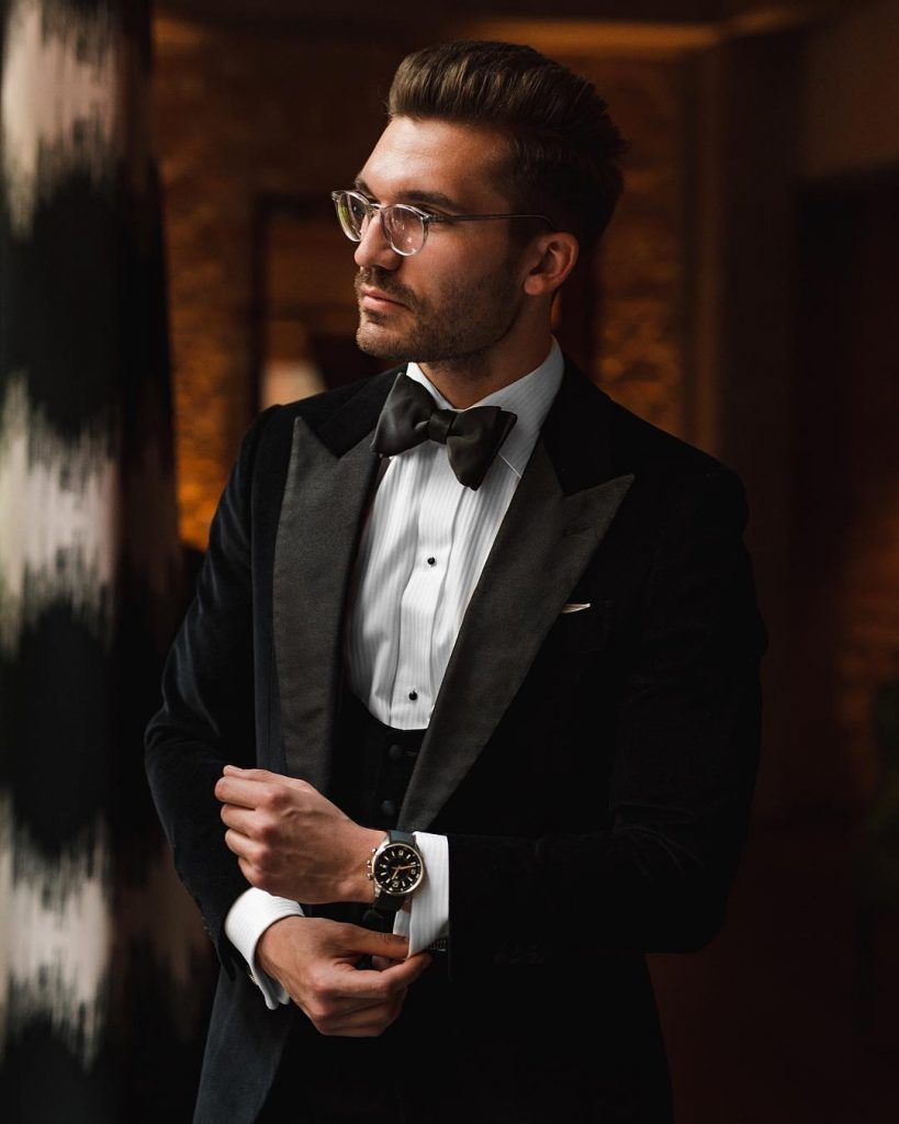 Black suit with a vest, and an elegant black bow tie