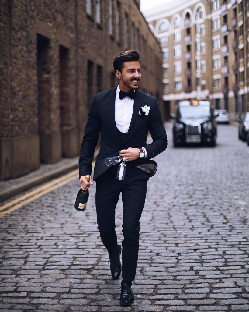 Black suit with a vest, white shirt, bow tie, and leather dress shoes