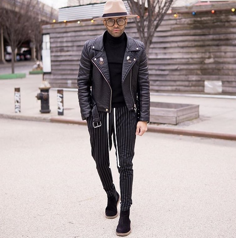 Leather biker jacket, sweater, dress pants, boots, hat
