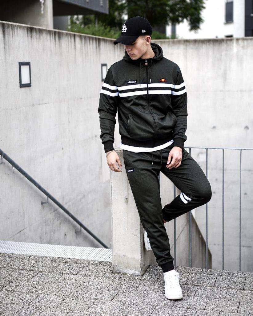 Black sport jacket, sport pants, sneaker, baseball cap