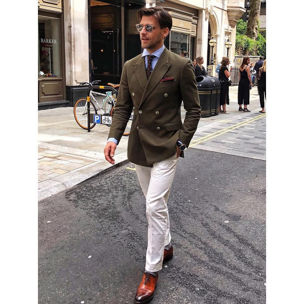 Double breasted olive green blazer, blue shirt, dotted tie, white dress pants, and leather shoes