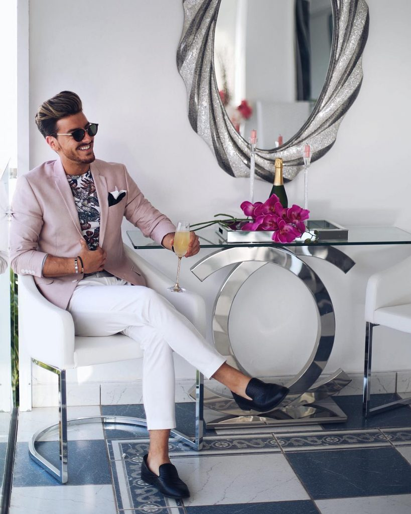 Pink blazer, printed crew-neck tee, white dress pants, and slip on shoes