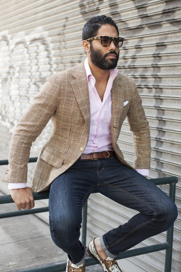 Brown checked shirt, pink shirt, brown leather belt, blue jeans, and loafers
