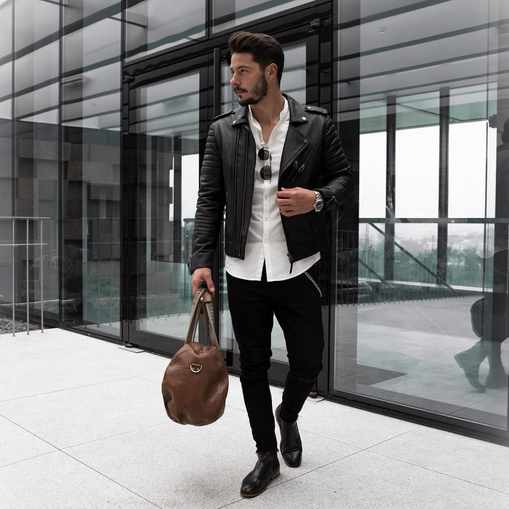 Leather biker jacket, white button-down shirt, black jeans, and leather boots