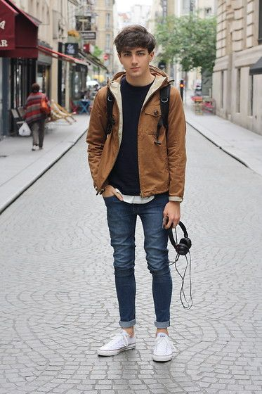 Black tee, brown jacket, blue jeans, and white canvas shoes