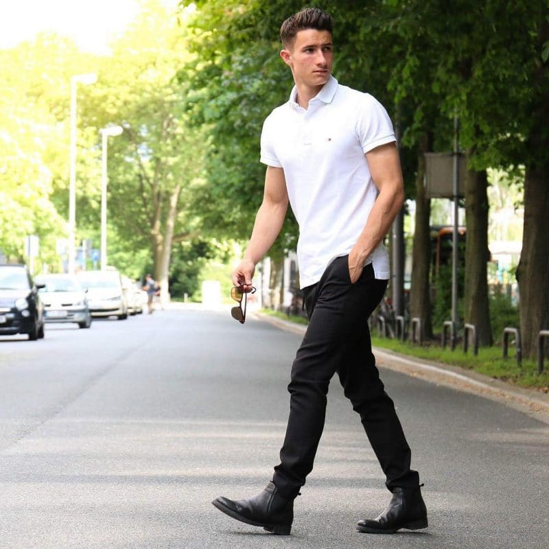White polo shirt, black trousers, and leather boots