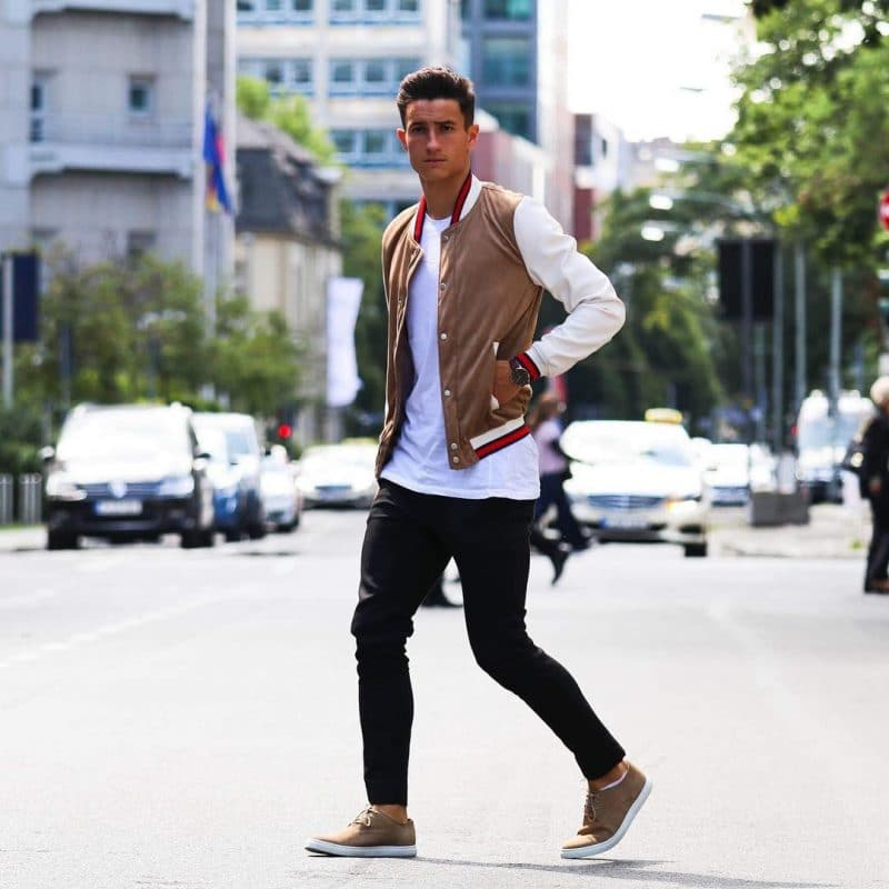 White tee, varsity jacket, black trousers and brown suede shoes