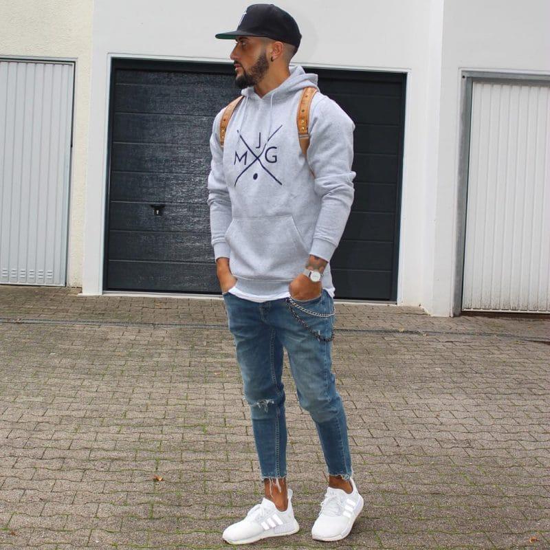 Gray sweatshirt, jeans, snapback cap, and sneaker