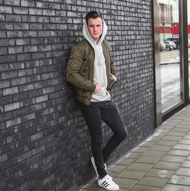 Olive green bomber jacket, gray sweatshirt, dark jeans, and sneaker