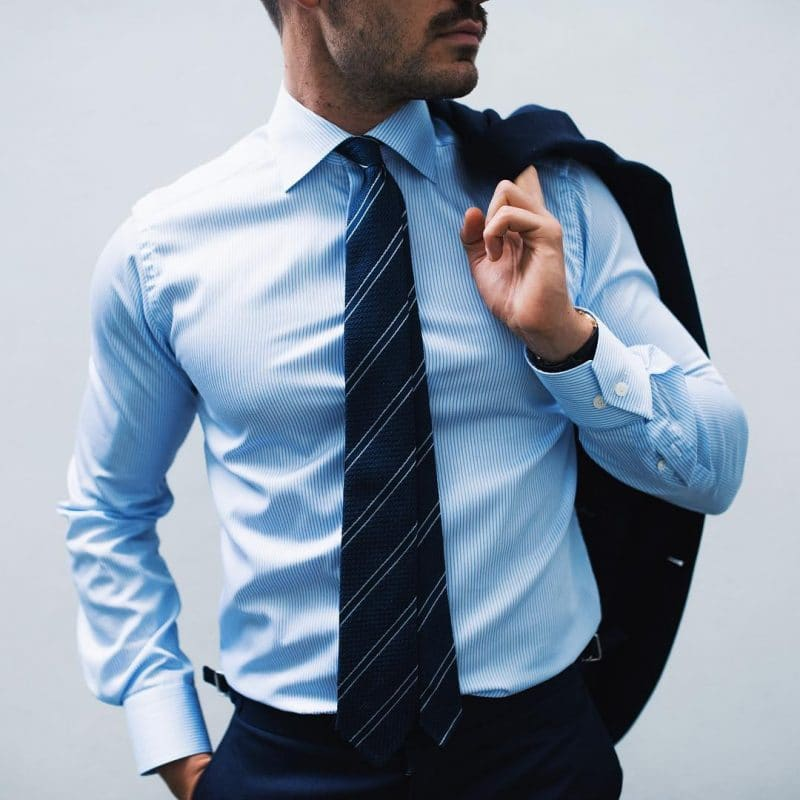 Blue shirt with striped tie and blue dress pants