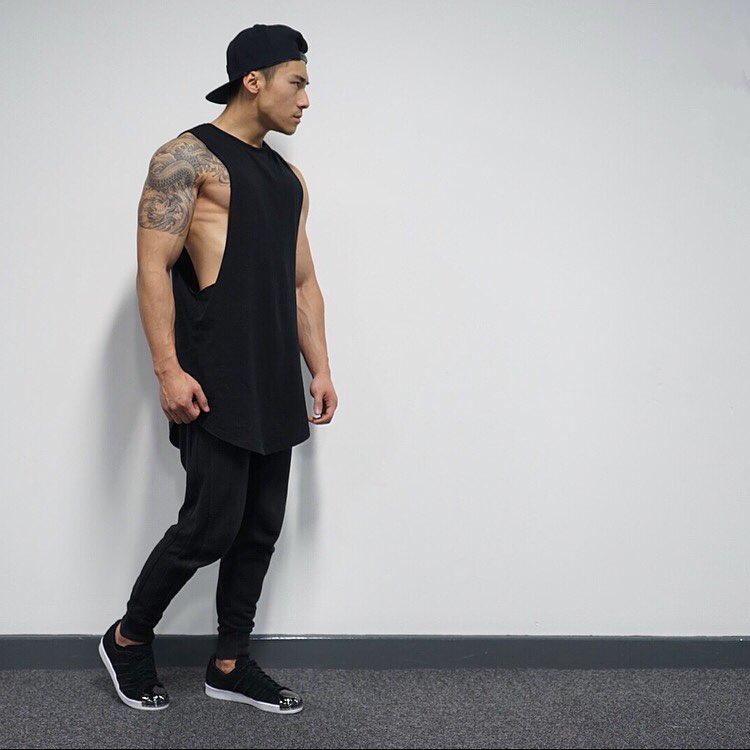 Black tank tops, sweatpants, sport shoes and snapback cap