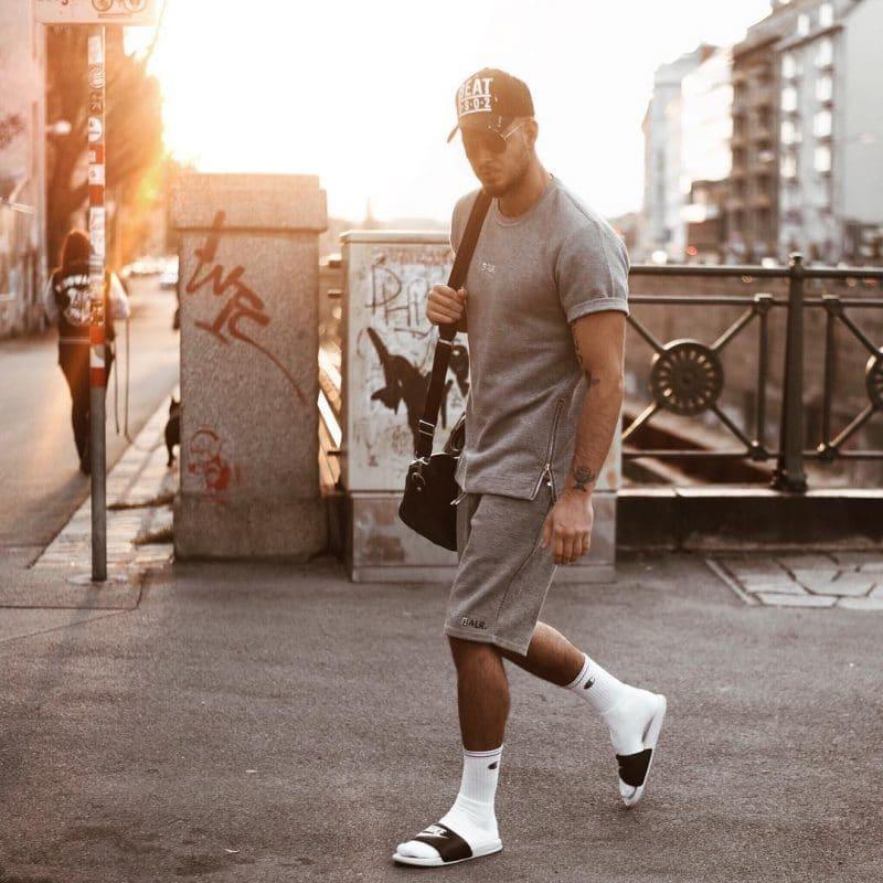Gray tee shirt, short sweatpants, baseball cap, sunglasses, socks and sandals