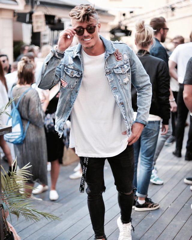 Blue denim jacket, white tee, black ripped jeans.