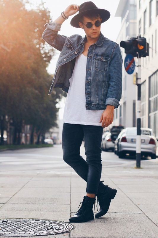 Blue denim jacket, white singlet, fedora hat, blue jeans, black boots