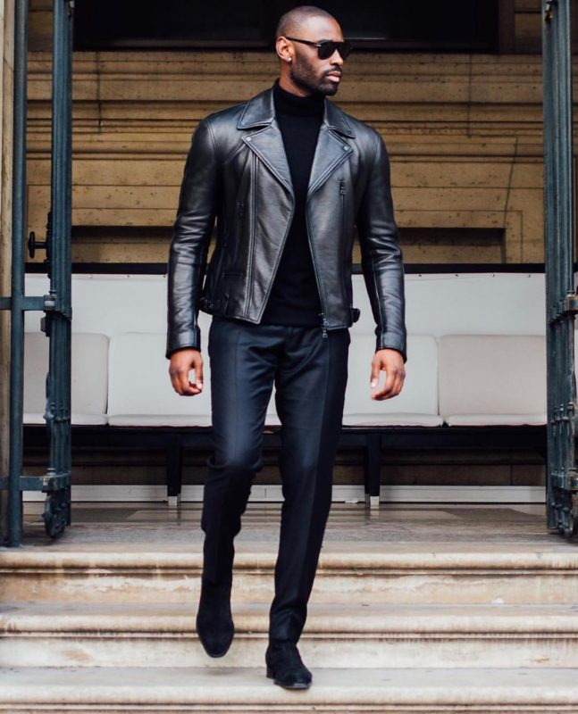Leather biker jacket, turtleneck sweater, dress pants, and leather boots