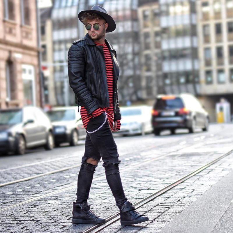 Stripe print tee, black leather jacket, black ripped jeans, fedora hat, and sneaker boots
