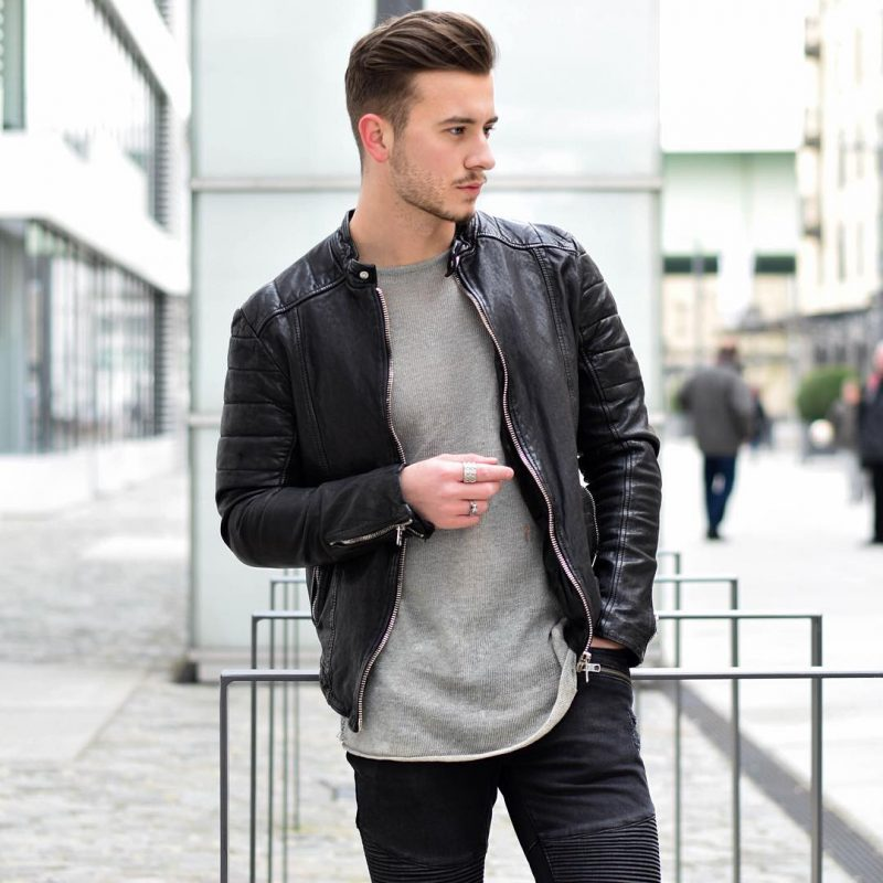 Leather bomber jacket, gray sweater, and black trousers