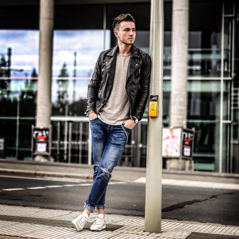 Leather biker jacket, beige tee, blue ripped jeans, and white sneaker