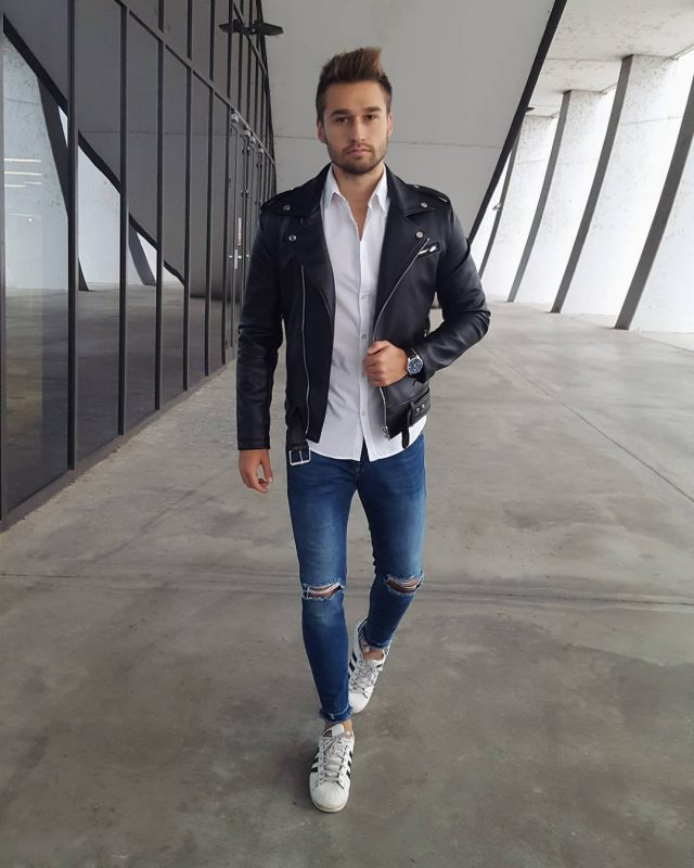 Leather biker jacket, button down white shirt, blue jeans, and white sneaker