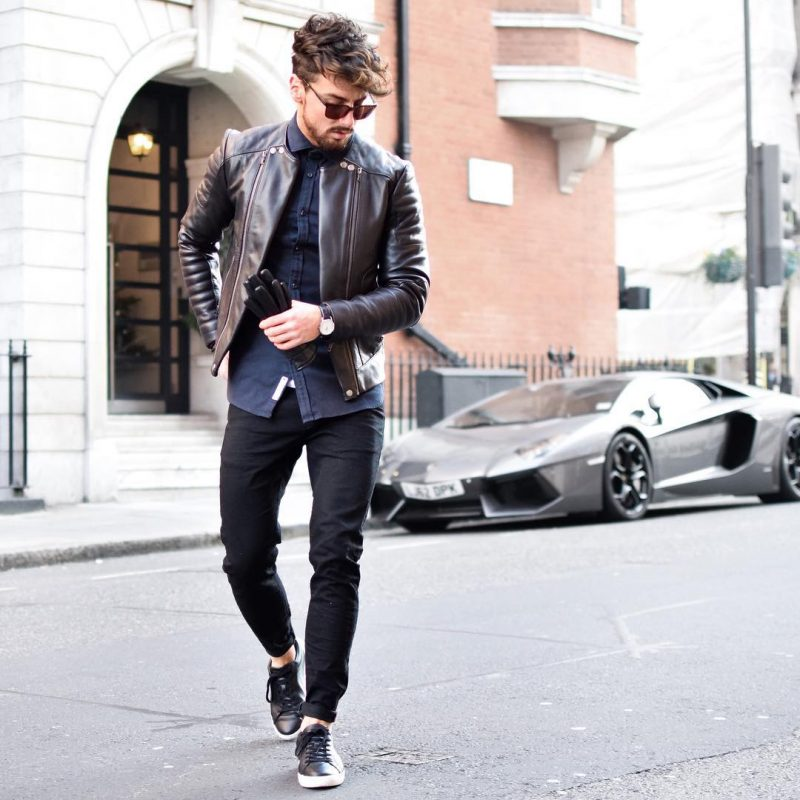 Dark brown leather jacket, blue button up shirt, black trousers, and sneaker