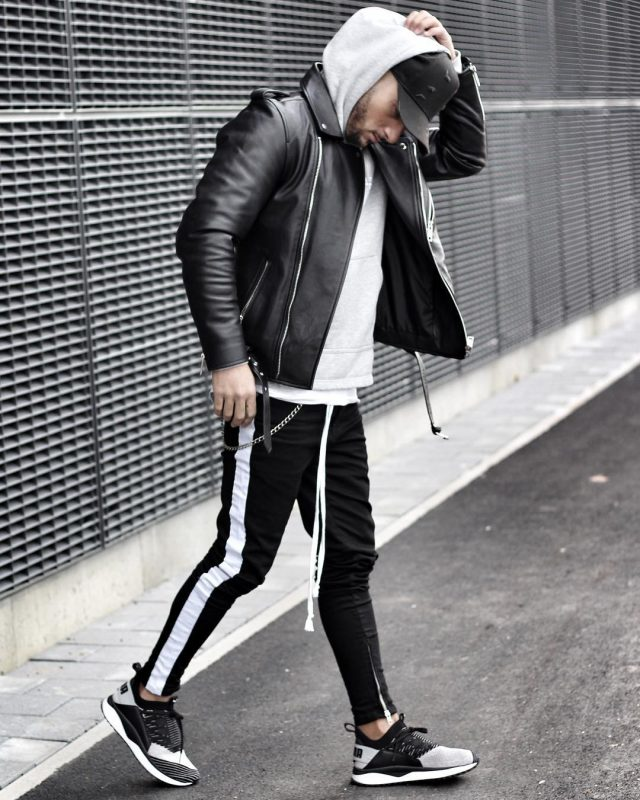 White hoodie sweatshirt, leather biker jacket, baseball cap, sweatpants, and sneaker