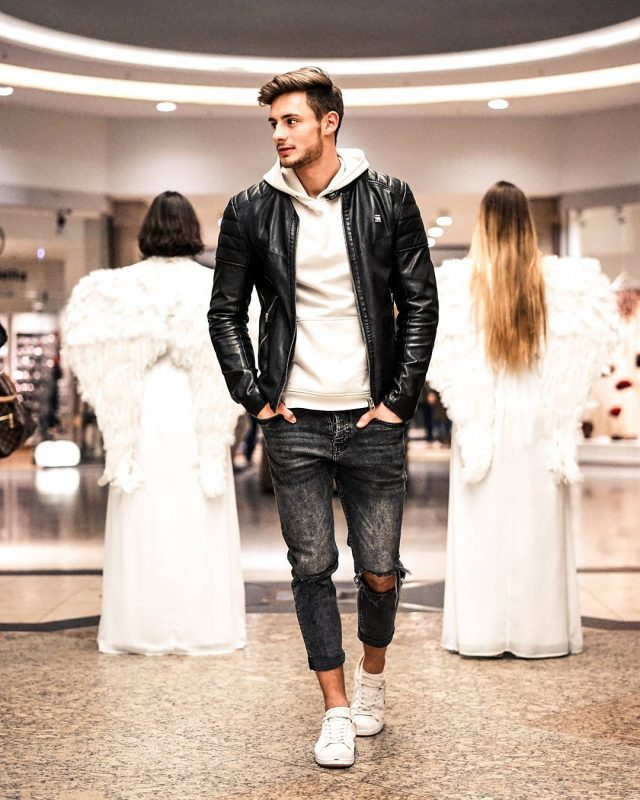 White hoodie sweatshirt, black leather bomber jacket, black ripped jeans, and white sneaker