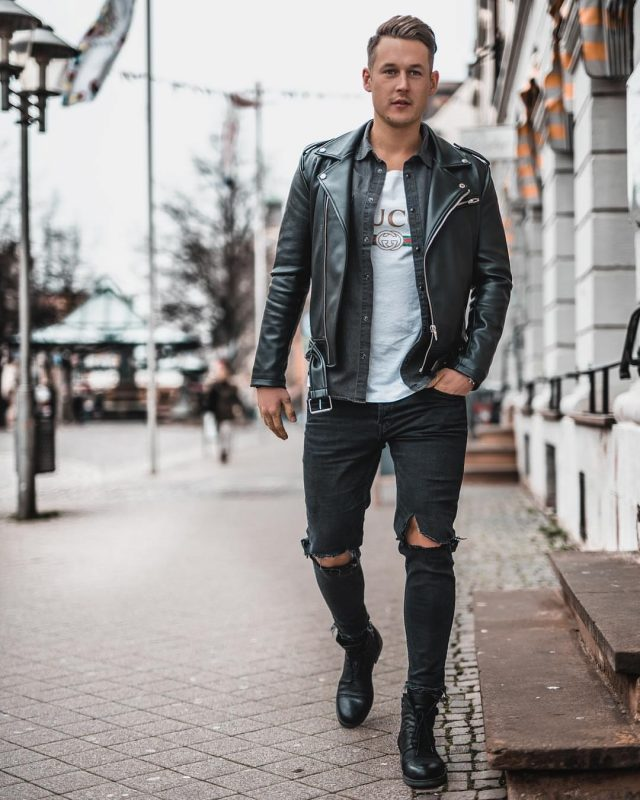 Dark gray overshirt, leather biker jacket, white print tee, black ripped jeans, and leather boots