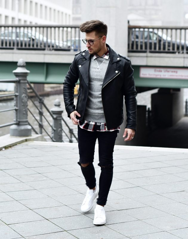 Checked shirt, gray sweater, leather biker jacket, ripped jeans, and white sneaker