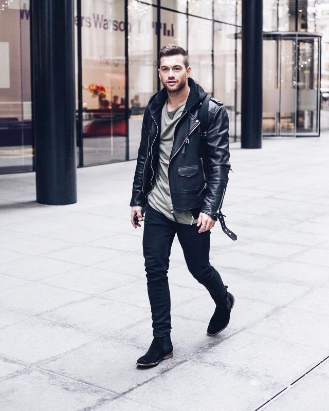 Leather biker jacket, hoodie jacket, olive green tee, black jeans, and Chelsea boots
