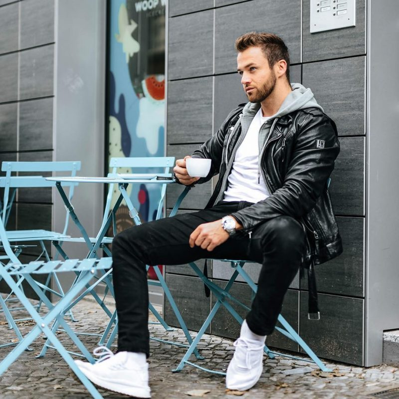 Leather biker jacket, light gray hoodie jacket, white tee, black trousers, and white sneaker