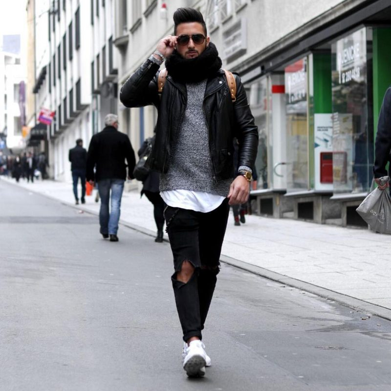 Gray textured sweater, leather biker jacket, white tee, scarf, ripped jeans, and white sneaker
